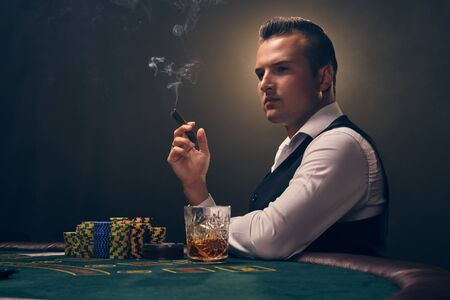 Wealthy man is smoking a cigar and playing poker with an excitement at a casino on black background. Imagens
