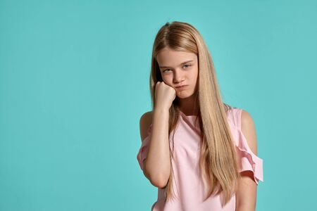 Studio portrait of a beautiful girl blonde teenager in a pink t-shirt posing over a blue background.