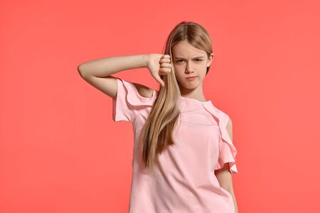 Studio portrait of a beautiful girl blonde teenager in a rosy t-shirt posing on pink background.