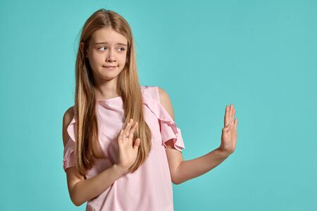 Studio portrait of a beautiful girl blonde teenager in a pink t-shirt posing over a blue background. 免版税图像