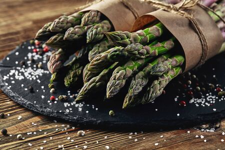 Bunches of an edible, palatable stems of asparagus on a stone slate, wooden background. Fresh, green vegetables, side view. Healthy eating. Fall harvest, agricultural farming concept.