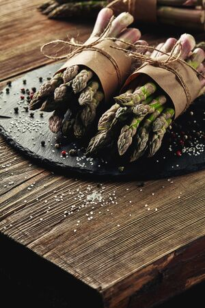 Bunches of an edible, delicious stems of asparagus on a stone slate, wooden table. Fresh, green vegetables with seasonings, top view. Healthy eating. Fall harvest, agricultural farming concept.
