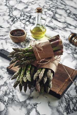 An edible, raw stems of asparagus on a marble background. Stock fotó