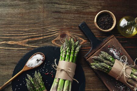 An edible, raw stems of asparagus on a wooden background. Archivio Fotografico