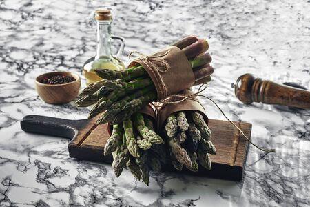 Een eetbare, rauwe asperges op een marmeren ondergrond.