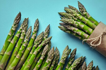 An edible, raw stems of asparagus on blue background.