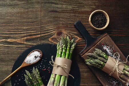 An edible, raw stems of asparagus on a wooden background. 免版税图像