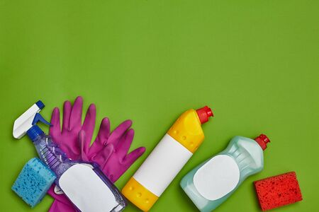 Detergents and cleaning accessories on a green background. Housekeeping concept. 版權商用圖片