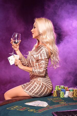 Blonde woman with a perfect hairstyle and bright make-up is posing with playing cards in her hands. Casino, poker. Standard-Bild