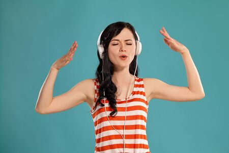 Studio photo of a gorgeous girl teenager posing over a blue background. 免版税图像
