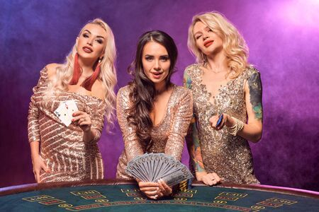 Beautiful girls with a perfect hairstyles and bright make-up are posing standing at a gambling table. Casino, poker.
