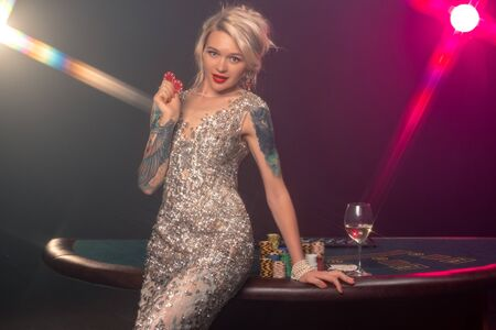 Blonde woman with a beautiful hairstyle and perfect make-up is posing with red gambling chips in her hands. Casino, poker.
