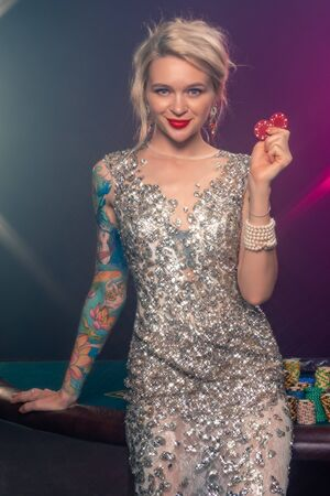 Blonde woman with a beautiful hairstyle and perfect make-up is posing with red gambling chips in her hands. Casino, poker. 版權商用圖片