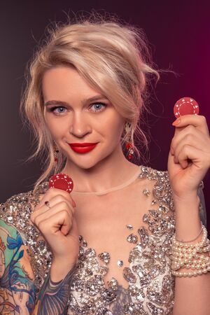 Blonde woman with a beautiful hairstyle and perfect make-up is posing with red gambling chips in her hands. Casino, poker. 免版税图像