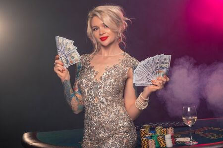 Blonde woman with a beautiful hairstyle and perfect make-up is posing with some money in her hands. Casino, poker.