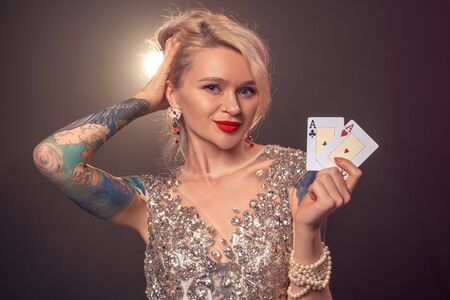 Blonde woman with a beautiful hairstyle and perfect make-up is posing with playing cards in her hands. Casino, poker.