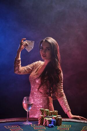 Brunette girl with a perfect hairstyle and bright make-up is posing with playing cards in her hands. Casino, poker. 免版税图像