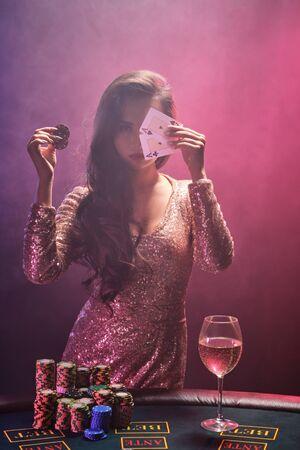 Brünettes Mädchen mit perfekter Frisur und hellem Make-up posiert mit Spielkarten und Spielmarken in den Händen. Kasino, Poker.