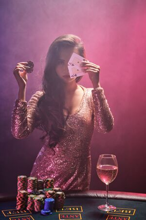 Brunetka z perfekcyjną fryzurą i jasnym makijażem pozuje z kartami do gry i żetonami do gry w dłoniach. Kasyno, poker.