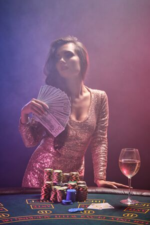 Brunette girl with a perfect hairstyle and bright make-up is posing with fan of hundred dollar bills in her hands. Casino, poker. 免版税图像