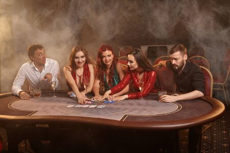 Group of a young wealthy friends are playing poker at a casino. Zdjęcie Seryjne
