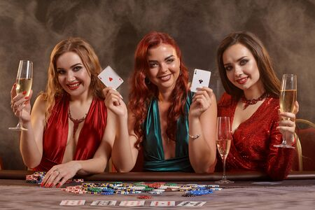Three beautiful young women are playing poker at a casino.