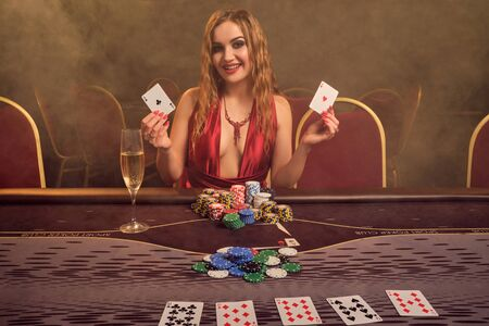 Charming woman with a beautiful hairstyle and perfect make-up is playing poker. Casino. 免版税图像