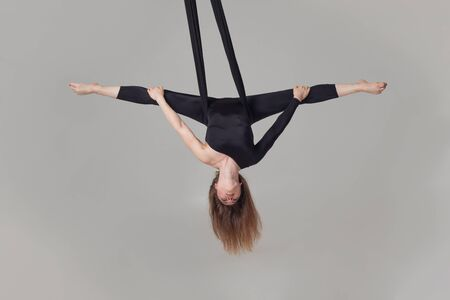 Beautiful girl in a black sport suit is performing an acrobatic elements in a studio.