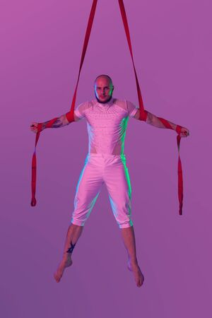 Athletic man in a white sport suit is performing an acrobatic elements in a studio.