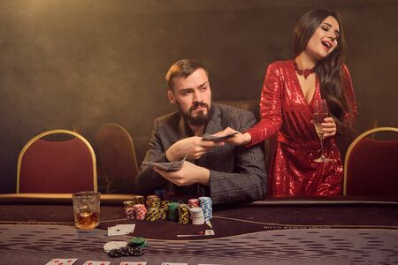 Charming wealthy couple are playing poker at a casino.