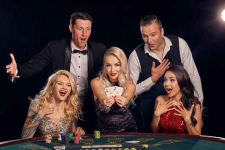 Grupa stylowych bogatych przyjaciół gra w pokera w kasynie.