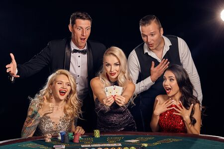 Un gruppo di amici ricchi alla moda sta giocando a poker in un casinò.