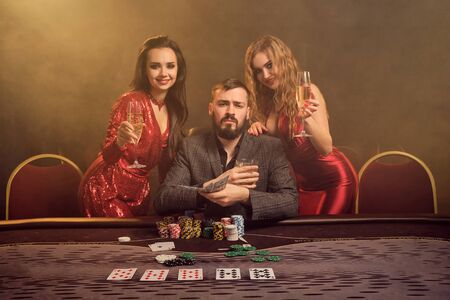 Group of a young wealthy friends are playing poker at a casino. Stock fotó