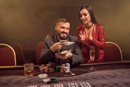 Charming wealthy couple are playing poker at a casino. 免版税图像