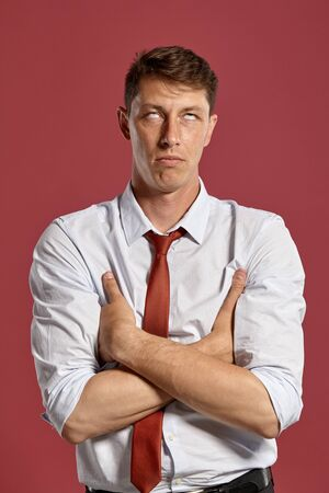 Portrait of a young brunet man posing in a studio against a red background.