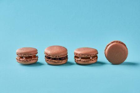 Close-up studio shot of tasty chocolate macarons on blue background.