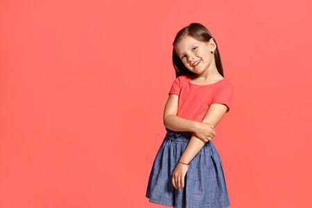 Close-up studio shot of beautiful brunette little girl posing against a blue background.