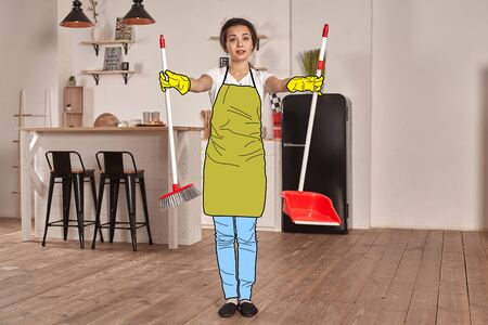 Beautiful girl in a cartoon jeans, an apron and rubber gloves is posing against a kitchen background with a brush and a dustpan.