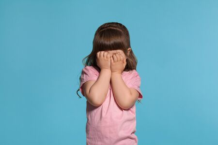 Beautiful little girl wearing in a pink t-shirt is posing against a blue studio background. Imagens