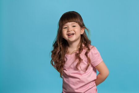 Beautiful little girl wearing in a pink t-shirt is posing against a blue studio background. Banco de Imagens