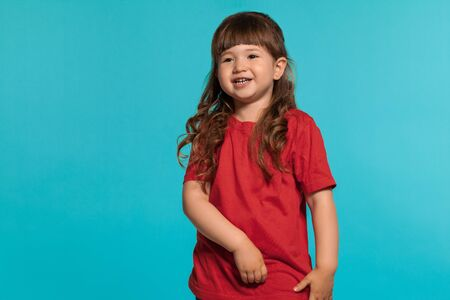 Beautiful little girl wearing in a red t-shirt is posing against a blue studio background.