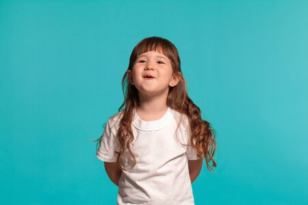 Beautiful little girl wearing in a white t-shirt is posing against a blue studio background.