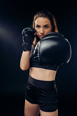 Athletic woman in boxing gloves is practicing karate in studio.