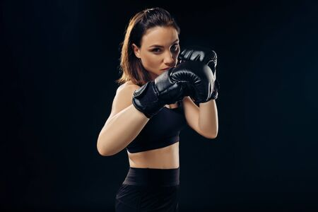Athletic woman in boxing gloves is practicing karate in studio. Banco de Imagens