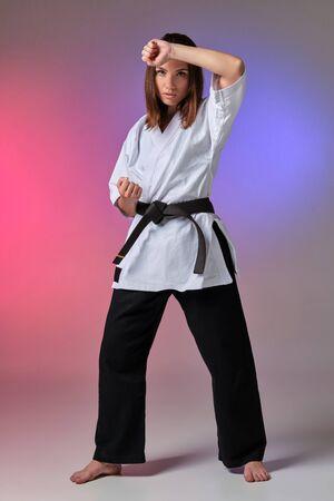 Mujer atlética en kimono tradicional está practicando karate en estudio.