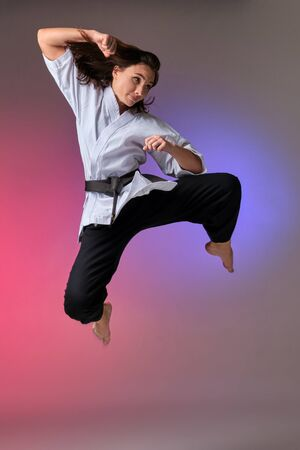 Athletic woman in traditional kimono is practicing karate in studio. Banco de Imagens
