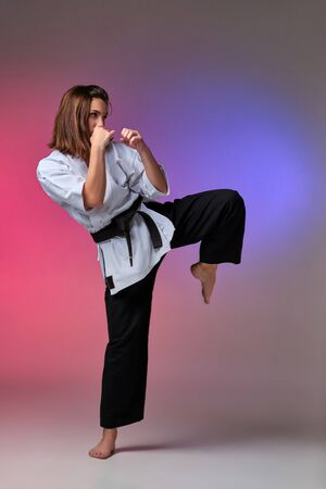 Athletic woman in traditional kimono is practicing karate in studio. Stok Fotoğraf