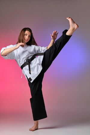 Athletic woman in traditional kimono is practicing karate in studio. 免版税图像