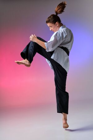 Athletic woman in traditional kimono is practicing karate in studio.