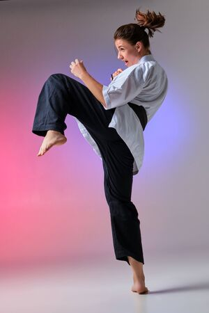 Athletic woman in traditional kimono is practicing karate in studio. Imagens